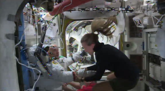 Astronaut Parmitano (left) re-entered the International Space Station following cancellation of a spacewalk on July 16, 2013, owing to water floating inside his helmet.