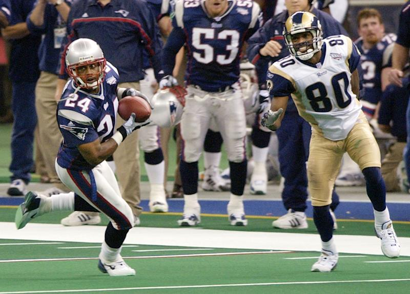 New England Patriots cornerback Ty Law (24) intercepts a pass from St. Louis Rams quarterback Kurt Warner as intended receiver Isaac Bruce (80) looks on during Super Bowl XXXVI, Sunday, Feb. 3, 2002, in New Orleans. (AP Photo/Kathy Willens)