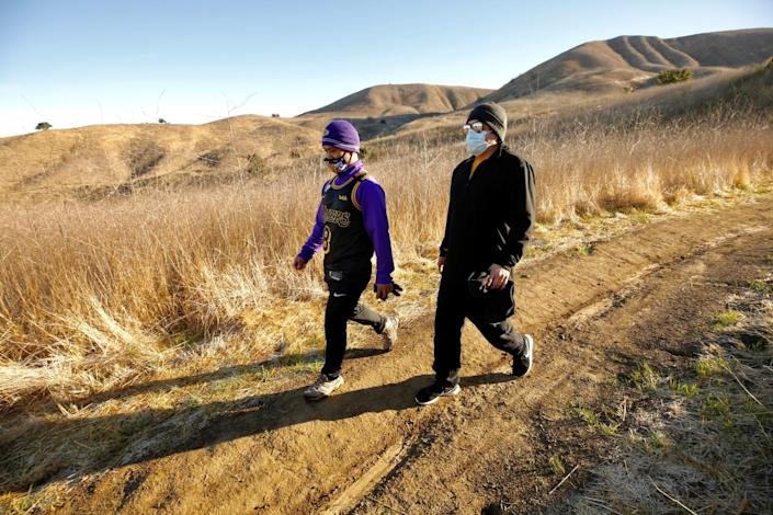 Men hike near where the helicopter carrying Kobe Bryant and eight others crashed last year in Calabasas.