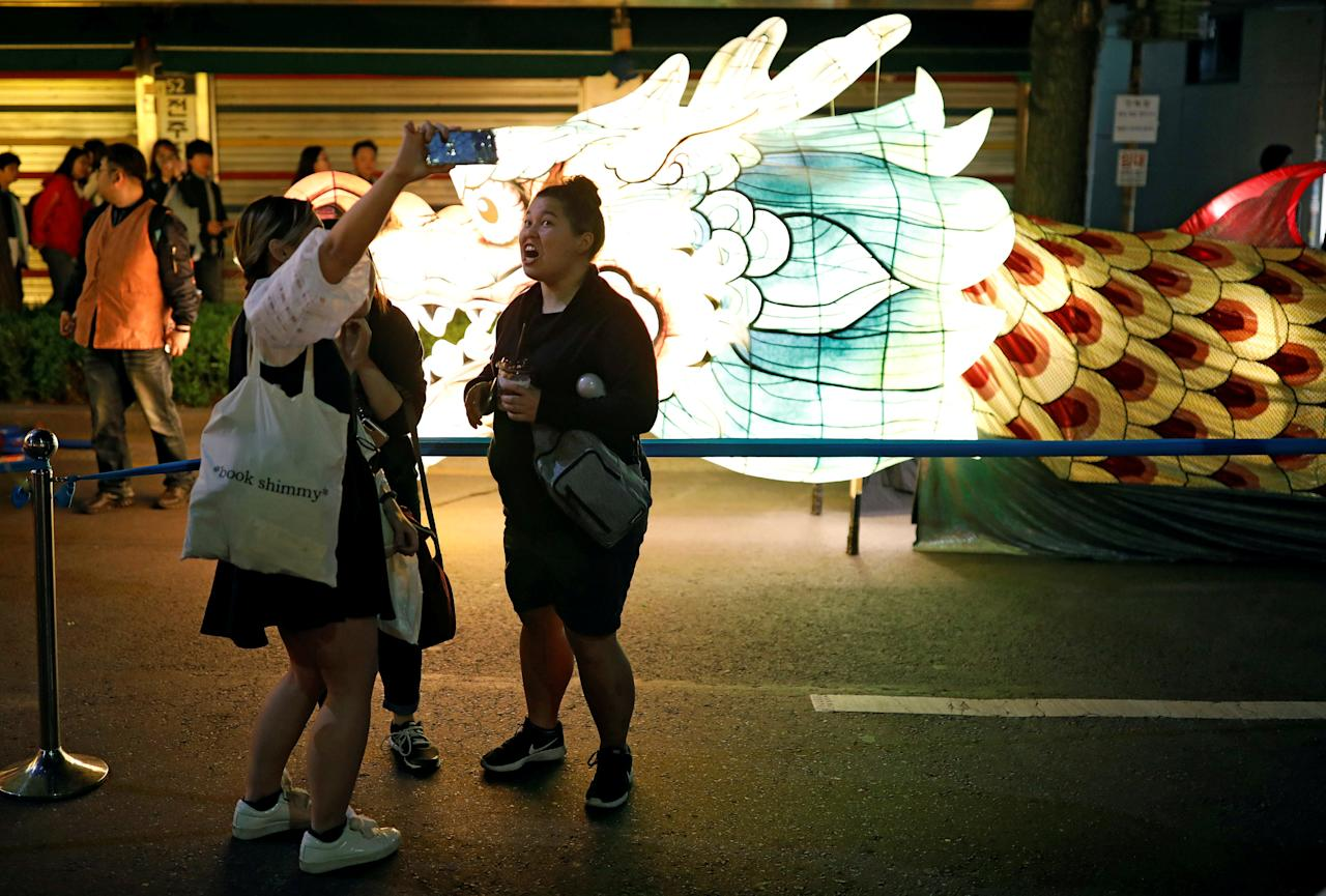 Tourists take a selfie in front of a giant dragon-shaped lantern after a Lotus Lantern parade in celebration of the upcoming birthday of Buddha in Seoul, South Korea April 29, 2017. REUTERS/Kim Hong-Ji