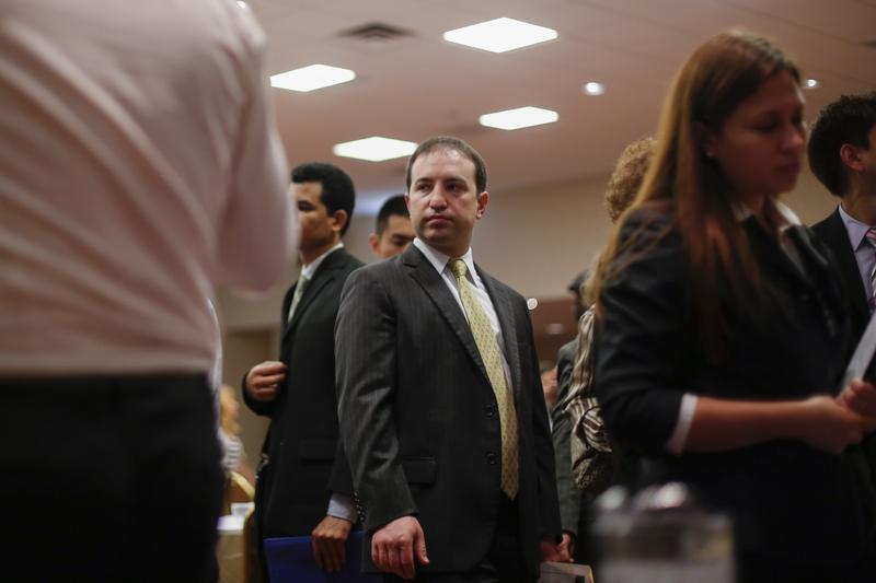Man waits in line to talk to recruiters while attending a job fair in New York