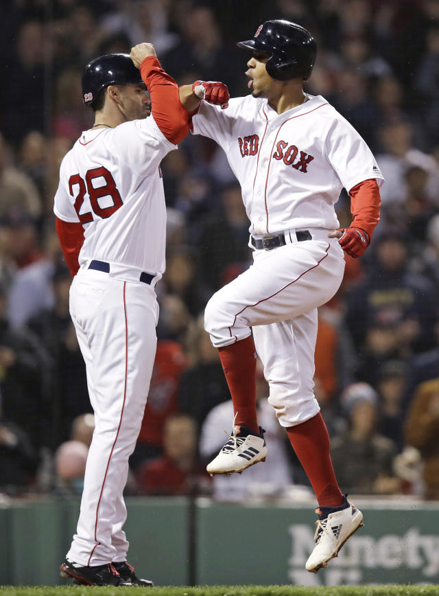 Boston Red Sox's Xander Bogaerts, right, is congratulated by J.D. Martinez as he crosses home plate after his three-run home run off Oakland Athletics relief pitcher Ryan Dull during the sixth inning of a baseball game at Fenway Park in Boston, Wednesday, May 16, 2018. (AP Photo/Charles Krupa)