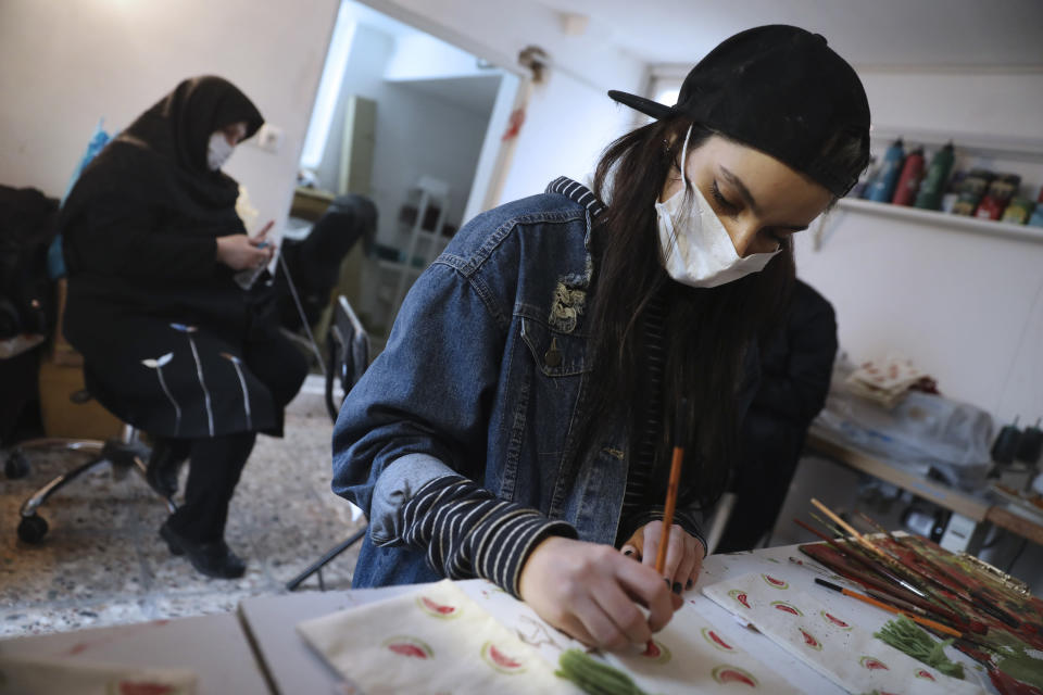 Bahareh Eskandarkhan paints on a cloth bag at a workshop of Bavar charity in Tehran, Iran, Monday, Nov. 23, 2020. As the coronavirus pandemic ravages Iran, a women's group hopes to empower its members by helping them make and sell face masks. (AP Photo/Vahid Salemi)