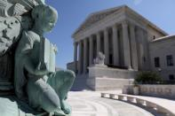 FILE PHOTO: A cherub figure with a book, symbolizing learning, is seen in a general view of the U.S. Supreme Court building in Washington