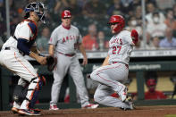 Los Angeles Angels' Mike Trout (27) scores as Houston Astros catcher Jason Castro waits for the throw during the fourth inning of a baseball game Monday, May 10, 2021, in Houston. (AP Photo/David J. Phillip)