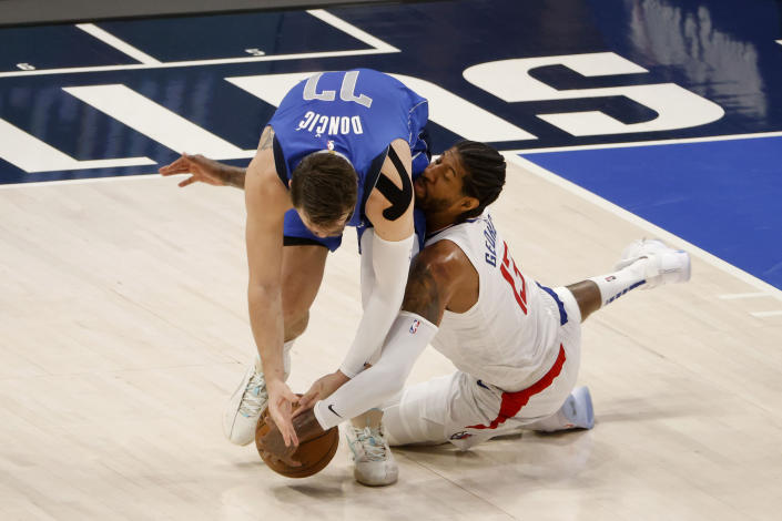 Dallas Mavericks guard Luka Doncic (77) and Los Angeles Clippers guard Paul George (13) go for the ball in the first half during Game 6 of an NBA basketball first-round playoff series in Dallas, Friday, June 4, 2021. (AP Photo/Michael Ainsworth)
