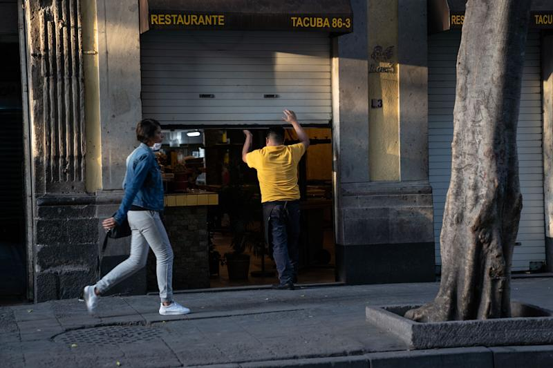 MEXICO CITY, MEXICO - MARCH 24: A man closes a store during phase two of contingency measures to avoid the spread of COVID-19 on March 24, 2020 in Mexico City, Mexico. Beginning Monday, Mexico City ordered the closure of museums, bars, gyms, churches, theaters, with the exception of restaurants, in an attempt to contain COVID-19 pandemic. (Photo by Toya Sarno Jordan/Getty Images)