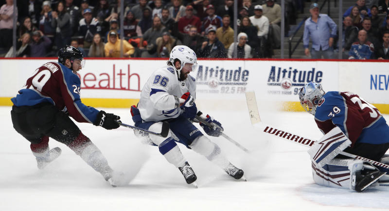Tampa Bay Lightning right wing Nikita Kucherov, center, scores the winning goal on Colorado Avalanche goaltender Pavel Francouz, right, after driving past center Nathan MacKinnon, left, and in overtime of an NHL hockey game Monday, Feb. 17, 2020, in Denver. The Lightning won 4-3 in overtime. (AP Photo/David Zalubowski)