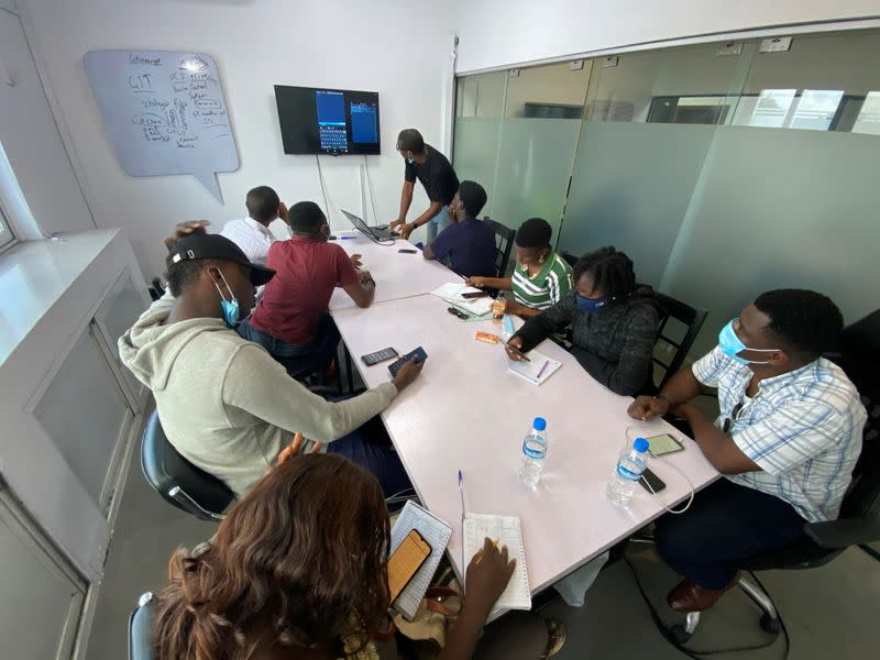 People use their phones during a coding training class in Lagos