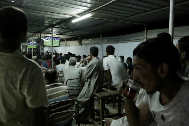In this May 2, 2018 photo, men watch the Liverpool vs. Roma match at a cafe in Mohamed Salah's hometown Nile delta village of Nagrig, Egypt. Residents boast of how the Liverpool winger has poured millions of pounds into the village, with the beneficiaries' list including a school, a mosque, a youth center and a dialysis machine at a nearby hospital. His success as a footballer in Europe's most attractive league has inspired many parents in Nagrig to send their children to soccer academies in the hope that maybe one day they can emulate his success. (AP Photo/Nariman El-Mofty)