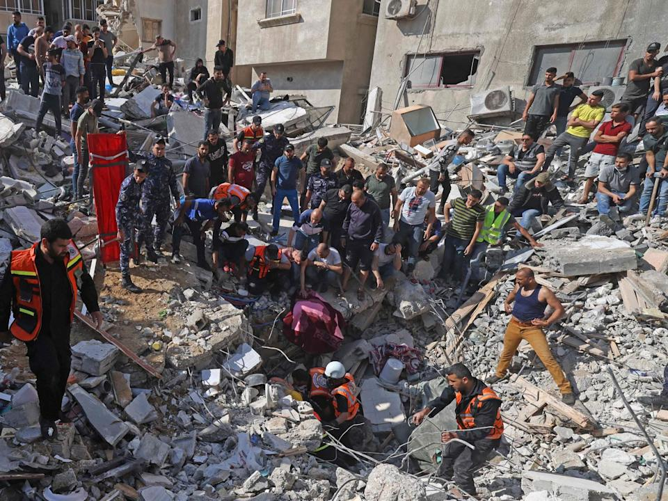 <p>Palestinian paramedics search for survivors under the rubble of a destroyed building in Gaza City on Sunday</p> (AFP/Getty)
