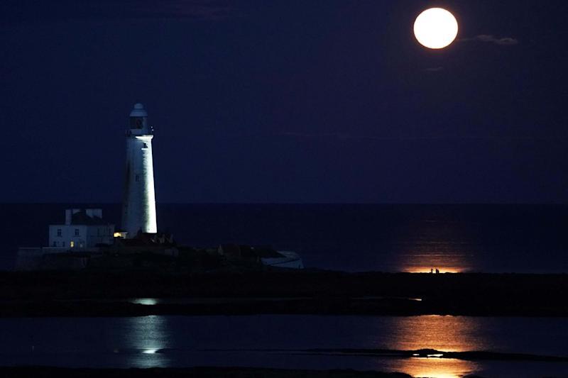 The August Full Moon, known as the Sturgeon Moon, rises above St Mary's Lighthouse in Whitley Bay: PA
