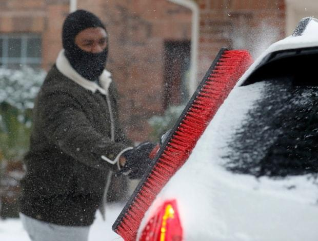 Patrick Minott uses a push broom to scrape snow and ice off his vehicles, on Monday in Kingwood, Texas.