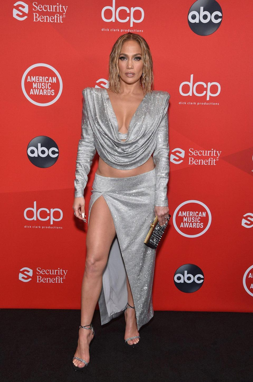 <p>Before taking the stage tonight, Jennifer Lopez arrived in a sparkling silver two-piece Balmain look (complete with the brand's signature strong shoulders) with a coordinating clutch and barely-there strappy heels. </p>