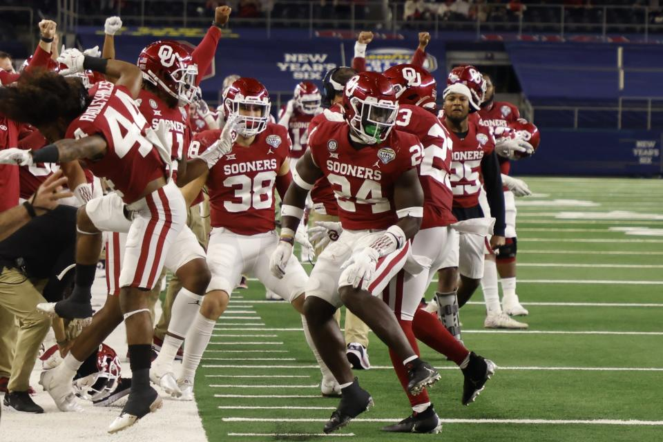FILE - Oklahoma team members on the sideline celebrate with linebacker Brian Asamoah (24) after Asamoah tackled Florida wide receiver Rick Wells short of the end zone on a fourth-down play in the second half of the Cotton Bowl NCAA college football game in Arlington, Texas, in this Wednesday, Dec. 30, 2020, file photo. Oklahoma is No. 2 in The Associated Press Tlop 25 preseason college football poll released Monday, Aug. 16, 2021. (AP Photo/Michael Ainsworth, File)