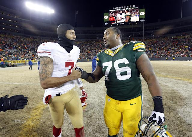 San Francisco 49ers quarterback Colin Kaepernick (7) talks to Green Bay Packers defensive end Mike Daniels (76) after an NFL wild-card playoff football game, Sunday, Jan. 5, 2014, in Green Bay, Wis. The 49ers won 23-20. (AP Photo/Mike Roemer)