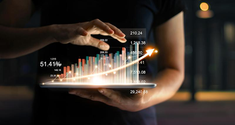 A hologram of a financial chart is projected over a tablet.