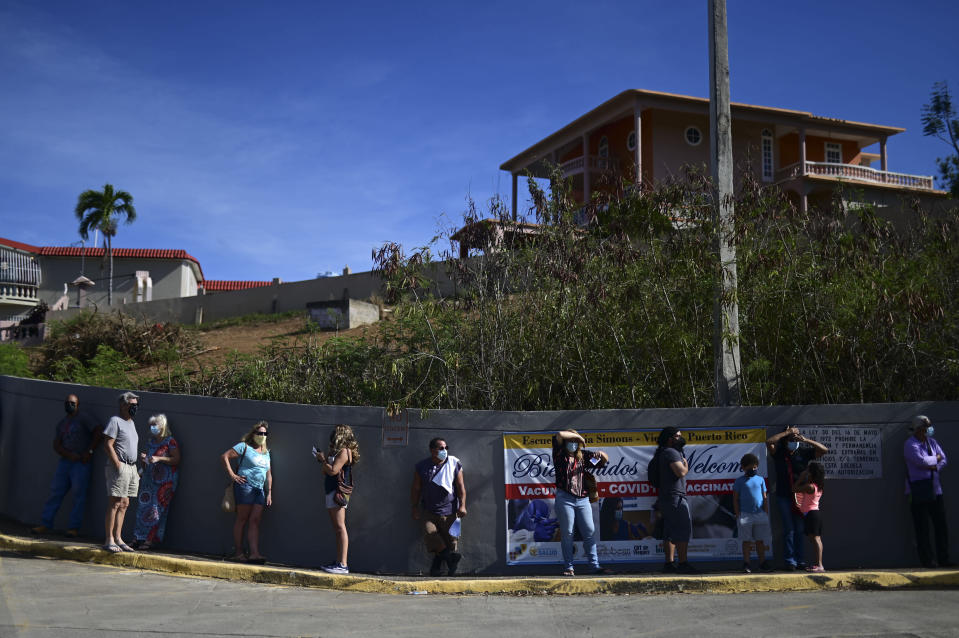 FILE - In this March 10, 2021 file photo, people stand in line outside the Maria Simmons elementary school waiting to be inoculated with the Moderna COVID-19 vaccine as part of a mass vaccination campaign, in Vieques, Puerto Rico. Puerto Rico seemed to be sprinting toward herd immunity this spring before people began letting their guard down against COVID-19 and new variants started spreading across the U.S. territory. (AP Photo/Carlos Giusti, File)