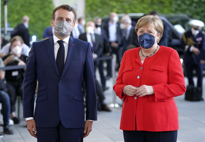 German Chancellor Angela Merkel, right, welcomes the President of France, Emmanuel Macron, left, for a meeting at the chancellery in Berlin, Germany, Friday, June 18, 2021. (AP Photo/Michael Sohn)