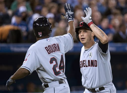 Cleveland Indians shortstop Asdrubal Cabrera, right, celebrates his two-run home run with teammate Michael Bourn, left, during fifth inning of an opening day baseball game against the Cleveland Indians in Toronto on Tuesday, April 2, 2013. (AP Photo/The Canadian Press, Nathan Denette)