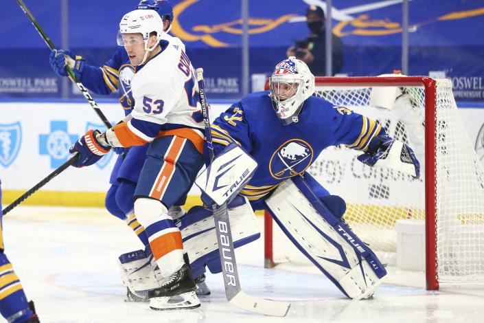 Buffalo Sabres goalie Michael Houser (32) is bumped into by New York Islanders forward Casey Cizikas (53) during the second period of an NHL hockey game, Monday, May 3, 2021, in Buffalo, N.Y. (AP Photo/Jeffrey T. Barnes)