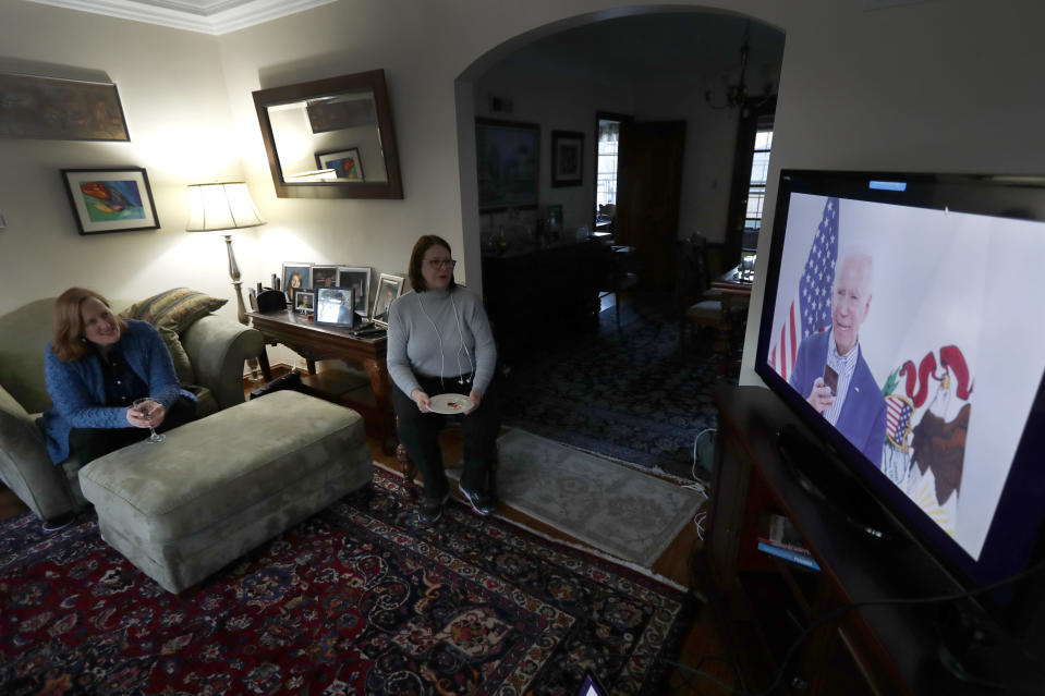 Lally Doerrer, right, and Katharine Hildebrand watch Joe Biden during his Illinois virtual town hall, in Doerrer's living room Friday, March 13, 2020, in Chicago. (AP Photo/Charles Rex Arbogast)