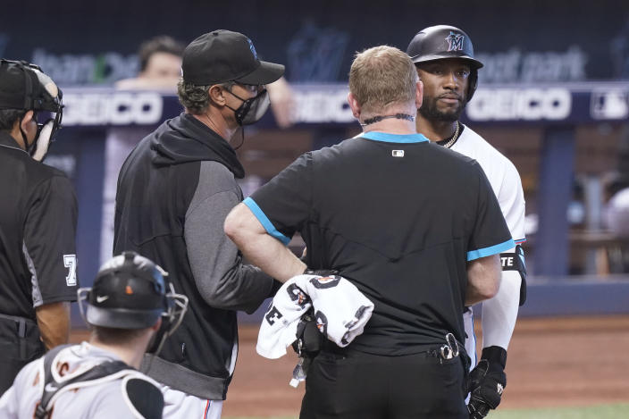 Miami Marlins manager Don Mattingly, center, and a trainer talk to batter Starling Marte before escorting him back to the dugout during the ninth inning of a baseball game against the San Francisco Giants, Sunday, April 18, 2021, in Miami. The Giants defeated the Marlins 1-0.(AP Photo/Marta Lavandier)