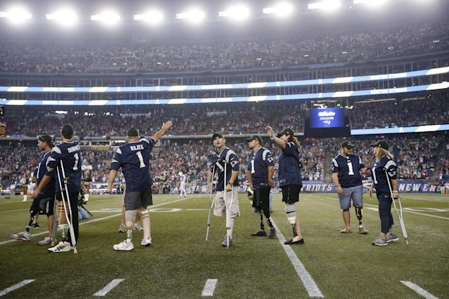 Wounded veterans and Boston Marathon bombing survivors who lost limbs are honored on the field before an NFL football game between the New England Patriots and the New York Jets on Thursday, Sept. 12, 2013, in Foxborough, Mass. (AP Photo/Elise Amendola)