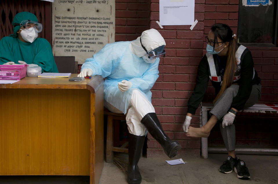"""Punam Karmacharya, 22, of the RNA-16 volunteer group, consults with a doctor about the pain on her feet at a hospital in Bhaktapur, Nepal. Tuesday, May 26, 2020. RNA-16 stands for """"Rescue and Awareness"""" and the 16 kinds of disasters they have prepared to deal with, from Nepal's devastating 2015 earthquake to road accidents. But the unique services of this group of three men and a woman in signature blue vests in the epidemic amount to a much greater sacrifice, said doctors, hospital officials and civic leaders. (AP Photo/Niranjan Shrestha)"""