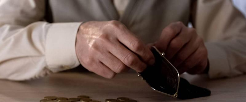 Older person putting coins into a wallet