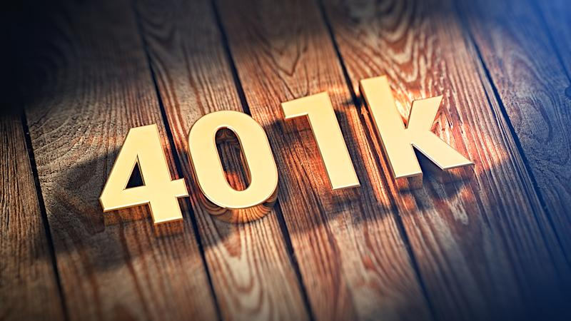 401k written out in gold block characters on top of a wooden plank background