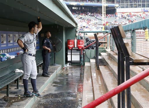 Seattle Mariners' Jesus Montero looks on from the dugout as rain falls during a weather delay before a baseball game against the Texas Rangers on Sunday, Sep. 16, 2012, in Arlington, Texas. (AP Photo/Jim Cowsert)