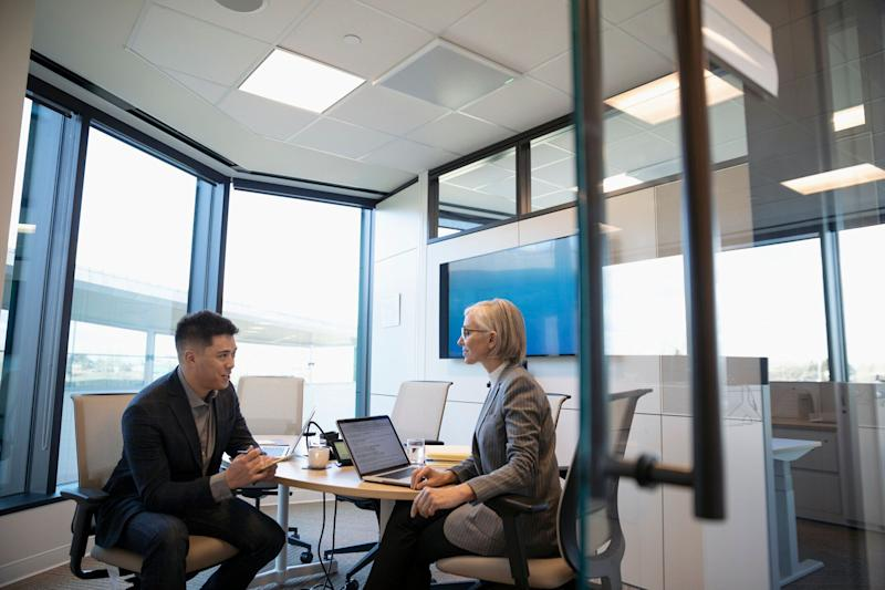 A photo of a man and a woman in a conference room.