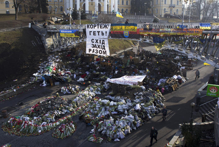 """People walk past a barricade located under a footbridge where thousands of flowers have been placed in memory of those killed during clashes in and around Kiev's Independence Square, Ukraine, Friday, March 7, 2014. The white banner at center reads, """"No more motorcades, East and West together!"""". (AP Photo/David Azia)"""