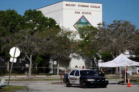 FILE PHOTO: Police officer Jamie Rubenstein stands guard in front of the Marjory Stoneman Douglas High School, after the police security perimeter was removed, following a mass shooting in Parkland