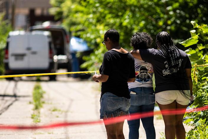 People watch as officials remove four bodies from a house on South Morgan Street in Chicago's South Side on Tuesday, June 15, 2021.