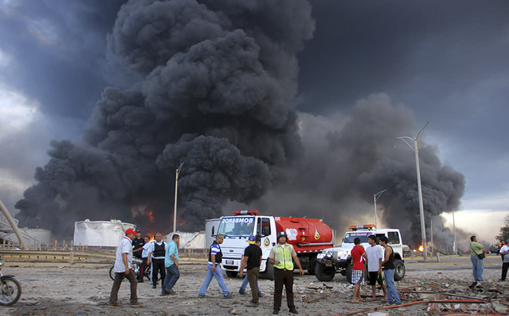 Firefighters and rescue teams work at the Amuay oil refinery after an explosion in Punto Fijo, Venezuela, Saturday, Aug. 25, 2012. A huge explosion rocked Venezuela's biggest oil refinery and unleashed a ferocious fire Saturday, killing over 20 people and injuring dozens in the deadliest disaster in memory for the country's key oil industry. (AP Photo/Diario EL Amanecer)