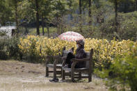 A woman wearing a face mask to help protect against the spread of the coronavirus, sits on a bench while maintaining social distancing at a park in Seoul, South Korea, Monday, Sept. 21, 2020. South Korea's daily virus tally has stayed below 100 for a second consecutive day, maintaining a slowing trend in fresh infections. (AP Photo/Lee Jin-man)