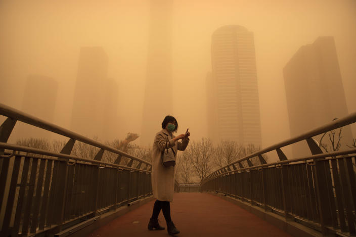 A woman walks along a pedestrian bridge amid a sandstorm during the morning rush hour in the central business district in Beijing, Monday, March 15, 2021. The sandstorm brought a tinted haze to Beijing's skies and sent air quality indices soaring on Monday. (AP Photo/Mark Schiefelbein)