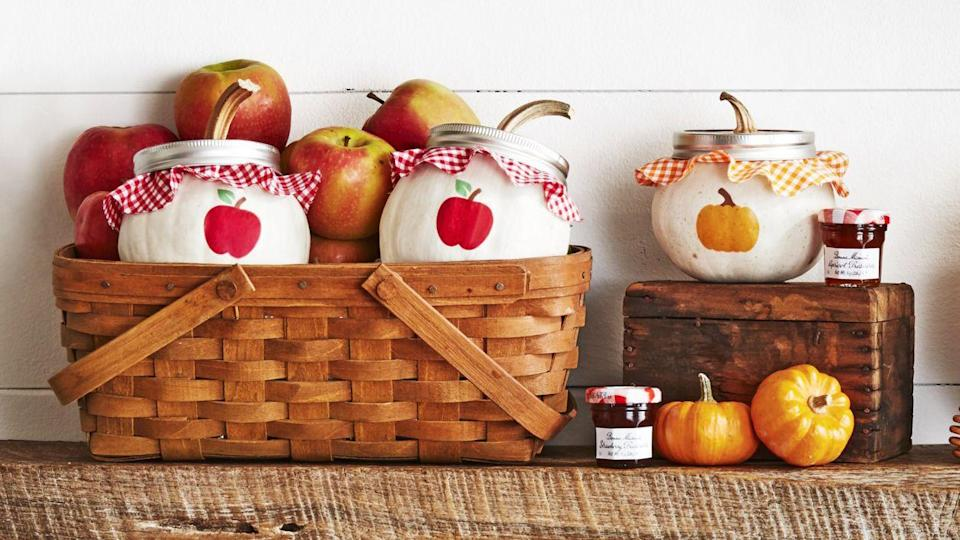 """<p>We're absolutely smitten with these pumpkin """"Mason jars."""" They're a combination of so many of our favorite things! </p><p><strong>Make the jars:</strong> Print pumpkin and apple <a href=""""https://www.countryliving.com/diy-crafts/how-to/a3048/halloween-templates-1009/"""" rel=""""nofollow noopener"""" target=""""_blank"""" data-ylk=""""slk:templates"""" class=""""link rapid-noclick-resp"""">templates</a> on removable tattoo paper. Attach to small white pumpkins per package directions. Remove the stems from pumpkins. Cut a piece of cardboard to fit into the opening of a wide-mouth Mason jar ring. Attach a round of gingham fabric, centering it, to the cardboard. Glue pumpkin stems in centers. Attach lids to tops of pumpkins. </p>"""