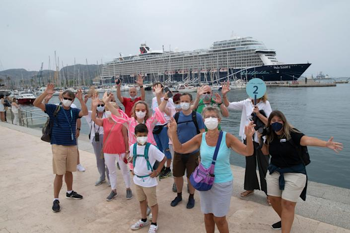 This image shows a group of people standing in front of a cruise ship waving to the camera.