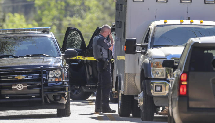 A Carroll County Sheriff deputies waits as the Georgia Bureau of Investigation investigates the scene after three metro Atlanta officers were injured Monday, April 12, 2021, after a police chase entered Carroll County, Ga., and a passenger fired multiple rounds with a rifle, officials said. Georgia authorities said one suspect was killed and the other arrested following the chase. (John Spink/Atlanta Journal-Constitution via AP)