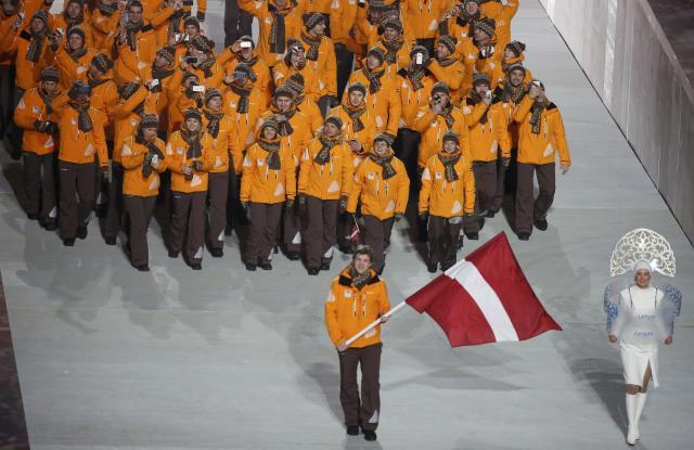 Latvia's flag-bearer Sandis Ozolins leads his country's contingent during the opening ceremony of the 2014 Sochi Winter Olympics, February 7, 2014. REUTERS/Lucy Nicholson (RUSSIA - Tags: OLYMPICS SPORT)
