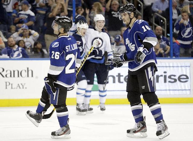 Tampa Bay Lightning right wing Martin St. Louis (26) and right wing Teddy Purcell (16) react as Winnipeg Jets center Mark Scheifele (55) celebrates his overtime goal with teammate Jacob Trouba (8) during an NHL hockey game Saturday, Dec. 7, 2013, in Tampa, Fla. The Jets won the game 2-1. (AP Photo/Chris O'Meara)
