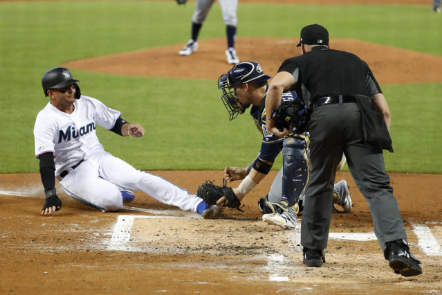 Milwaukee Brewers catcher Yasmani Grandal tags out Miami Marlins' Miguel Rojas at home plate as umpire Shane Livensparger looks on during the first inning of a baseball game, Thursday, Sept. 12, 2019, in Miami. (AP Photo/Wilfredo Lee)