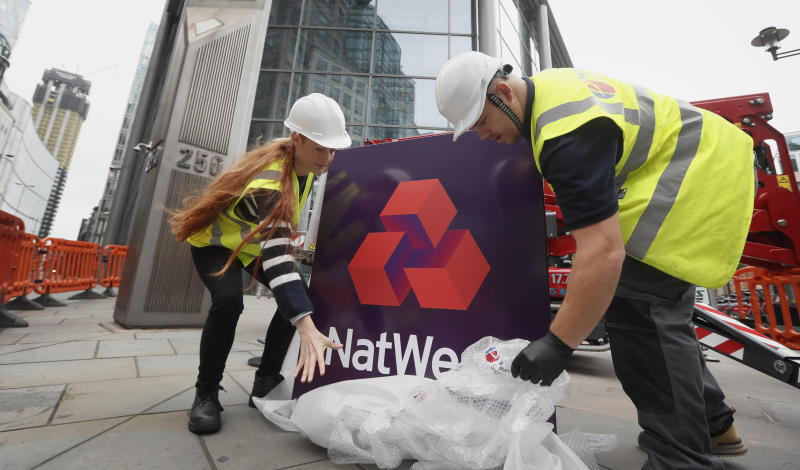 Workers unwrap a NatWest Bank sign before it is erected at 250 Bishopsgate in London, Saturday, Oct. 7, 2017. Natwest bank is becoming the high street (retail) face of the RBS group. A move from the global Royal Bank of Scotland institution to the more locally focused Natwest. The move is a sign of change in the banking world following the financial crisis. (AP Photo/Kirsty Wigglesworth)