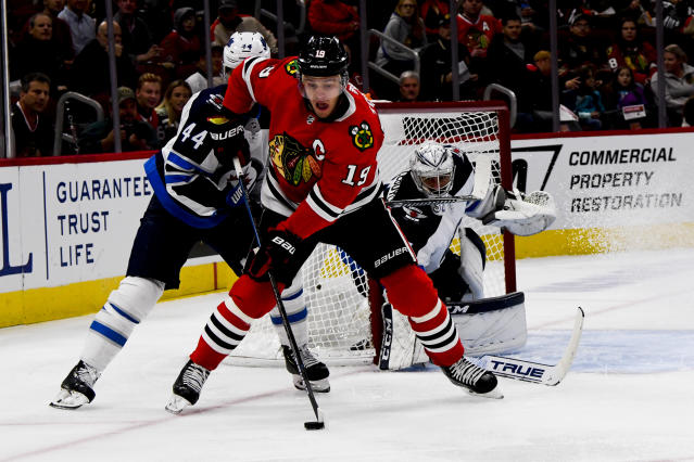 Chicago Blackhawks center Jonathan Toews (19) and Winnipeg Jets defenseman Josh Morrissey (44) fight for the puck during the first period of an NHL hockey game Saturday, Oct. 12, 2019, in Chicago. (AP Photo/Matt Marton)
