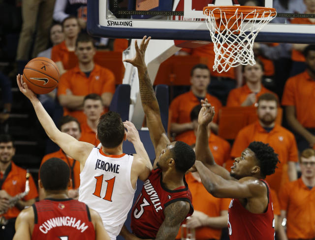 Virginia guard Ty Jerome (11) goes up to shoot as Louisville forward V.J. King (13) and Louisville center Steven Enoch, right defend during the first half of an NCAA college basketball game in Charlottesville, Va., Saturday, March 9, 2019. (AP Photo/Steve Helber)