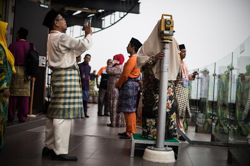 A visitor uses a Theodolite before the sighting of the new moon of Ramadan, on the observation deck of the KL Tower in Kuala Lumpur, on June 27, 2014 (AFP Photo/Mohd Rasfan)