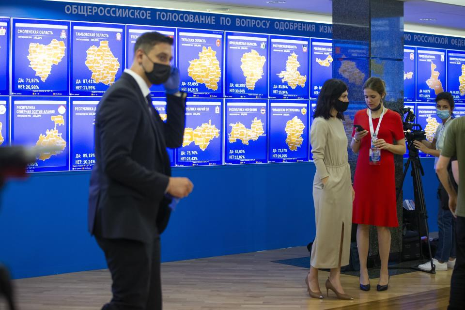 Staff members of the Russian Central Election Commission, wearing face masks and gloves to protect against coronavirus, gather prior to a news conference with Ella Pamfilova, head of Russian Central Election Commission, in front of an electronic screen showing the results of constitution vote in Moscow, Russia, Thursday, July 2, 2020. Almost 78% of voters in Russia have approved amendments to the country's constitution that will allow President Vladimir Putin to stay in power until 2036, Russian election officials said Thursday after all the votes were counted. Kremlin critics said the vote was rigged. (AP Photo/Alexander Zemlianichenko)
